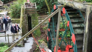 group looking at working waterwheel